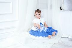 Little girl in bright room. Funny and cute brunette little smiling girl sits on fluffy carpet in bright room Royalty Free Stock Photos