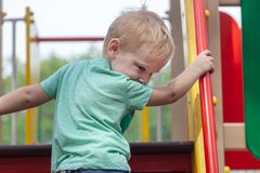 Funny cute caucasian blonde baby boy plays on the playground, climbing to upstair. royalty free stock images