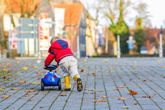 Funny cute child in red jacket driving blue toy car and having f Royalty Free Stock Photo
