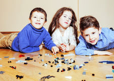 Funny cute children playing toys at home, boys and girl smiling, first education role close up, lifestyle people concept Stock Photo