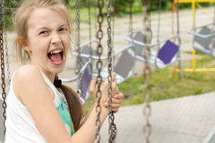 Funny cute girl screaming in the swing ride Royalty Free Stock Photos