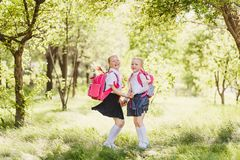 Funny cute girls in school uniform and with backpacks. Outdoors Royalty Free Stock Image