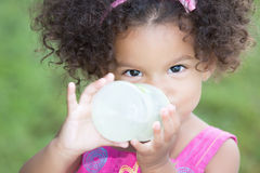 Funny and cute latin girl drinking from a baby bottle Stock Image