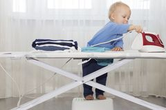 Funny cute little baby boy housekeeper ironing clothes. Kid engaged in domestic work.  Royalty Free Stock Photos