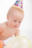 Funny cute little baby playing with yellow balloon. Stock Photos