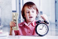 Funny cute little business child girl holding a clock and US Dollars in office. Time is money concept.