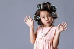 Cute little child girl in pink dress and hair curlers. Funny cute little child girl in pink dress and hair curlers posing on gray background. Human emotions and royalty free stock images