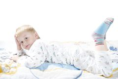 Funny cute little child in pyjamas with blonde hair lies on a bed Royalty Free Stock Photos