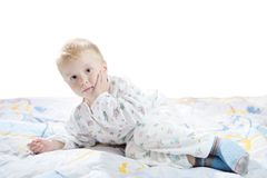 Funny cute little child in pyjamas with blonde hair lies on a bed Royalty Free Stock Photo