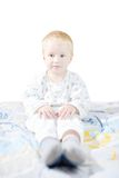 Funny cute little child in pyjamas with blonde hair sits on a bed Stock Images