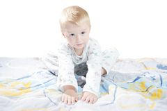 Funny cute little child in pyjamas with blonde hair sits on a bed Stock Photos