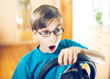 Funny cute little child sitting behind a computer driving wheel playing game Stock Photos