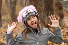 Funny cute little girl in funny owl hat smaking faces. In the autumn forest, outdoor stock photography