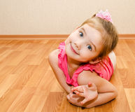 Funny little girl lies on a house floor Royalty Free Stock Image