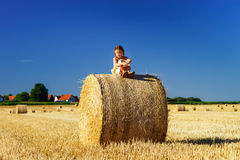 Funny cute little girl posing on the haystack in summer field Stock Photos
