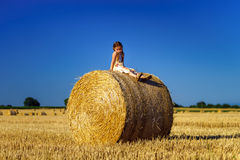 Funny cute little girl posing on the haystack in summer field Royalty Free Stock Images