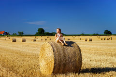 Funny cute little girl posing on the haystack in summer field Stock Photography