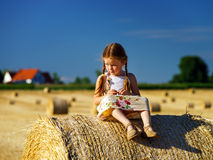 Funny cute little girl posing on the haystack in summer field Royalty Free Stock Photos