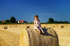Funny cute little girl posing on the haystack in summer field Stock Photo