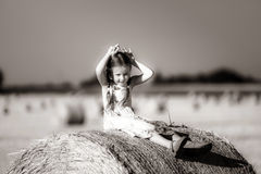 Funny cute little girl posing on the haystack in summer field Royalty Free Stock Photography