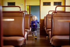 Funny cute little girl running through an empty train waggon. Happy healthy toddler child having fun on family travel royalty free stock photo