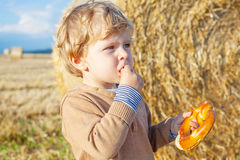 Funny cute little kid boy eating pretzel on late summer day on w Royalty Free Stock Photos