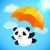 Funny cute panda flying with orange parachute Stock Images