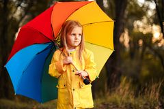 Funny cute toddler girl wearing waterproof coat with colorful umbrella royalty free stock photos