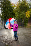 Funny cute toddler girl wearing waterproof coat with colorful umbrella stock photos