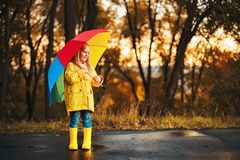Funny cute toddler girl wearing waterproof coat with colorful umbrella royalty free stock images