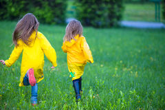 Funny cute toddler girls wearing waterproof coat playing outdoors by rainy and sunny day Stock Images