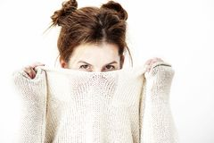 Funny cute young woman is smiling into the camera while covering her face with the collar of her sweater. Royalty Free Stock Images