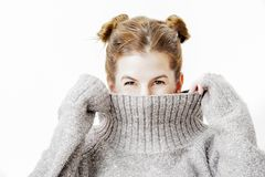 Funny cute young woman is smiling into the camera while covering her face with the collar of her sweater. Stock Photo
