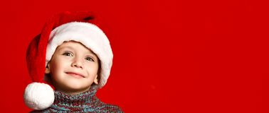 Funny smiling joyful child boy in Santa red hat stock photo