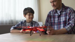 Funny dad operating quadcopter at home, happy son looking at new drone, game stock footage