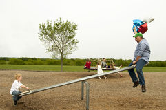 Funny dad on teeter-totter Stock Photo