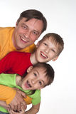 Funny dad and two sons. In color shirts Royalty Free Stock Photos