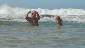 Funny daddy and son spend time in sea at resort slow motion