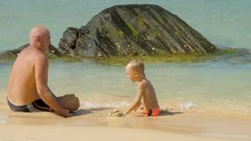 Funny daddy throws wet sand in son on tropical resort