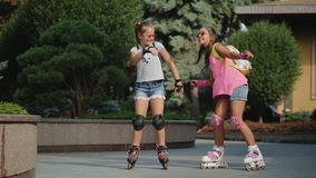Funny dance of two young girls roller skating in a city park