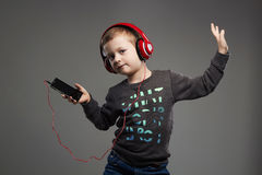 Funny dancing child.little boy in headphones.kid listening music Royalty Free Stock Image