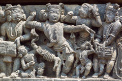 Funny dancing people in traditional Indian clothes. Relief of 12th century Hindu temple Hoysaleshwara in Halebidu, India Royalty Free Stock Photos