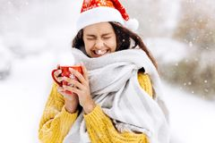 Funny dark-haired girl in a yellow sweater, a white scarf in Santa Claus hat is standing with a red mug on a snowy stock photography