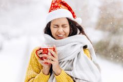 Funny dark-haired girl in a yellow sweater, a white scarf in Santa Claus hat is standing with a red mug on a snowy royalty free stock photo
