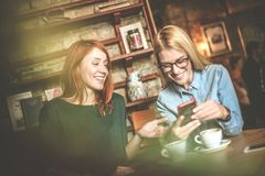 Funny day at cafe. Best friends. Two smiling best friends at cafe using smart phone. Reading messages stock photos