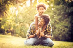 Funny day with father. African American father with his daughter playing together in park royalty free stock images