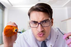 The funny dentist with curing light in medical concept Stock Images