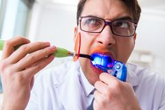 The funny dentist with curing light in medical concept royalty free stock image