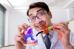 The funny dentist with curing light in medical concept Stock Photo