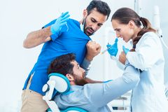 Funny dentist or dental surgeon acting crazy in front of his assistant royalty free stock images